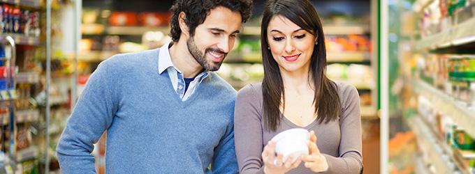 couple lisant une étiquette de produit dans un supermarché